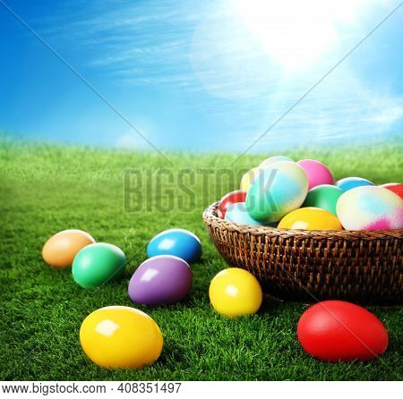 Wicker Basket With Easter Eggs On Green Grass Outdoors