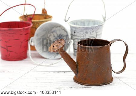 Rusted Old Miniature Watering Can Wiht Bucket On Wooden White Table