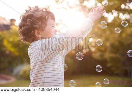 Young Boy Having Fun In Garden Chasing And Bursting Bubbles