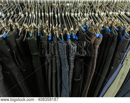 A Row Of Hangers With Cheap Pants In The Store In A Market. Close-upw With Selective Focus.