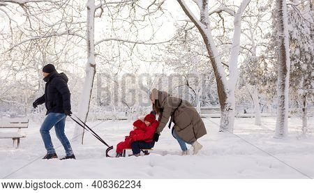 Dad Rolls His Three-year-old Daughter In A Sleigh Through The Snow In A Winter Park Between The Tree