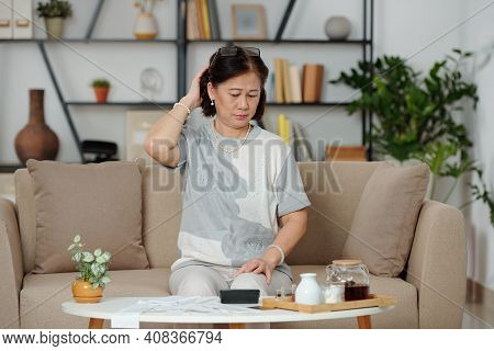 Confused Pensive Senior Asian Woman Looking At Many Bills On Coffee Table In Front Of Her