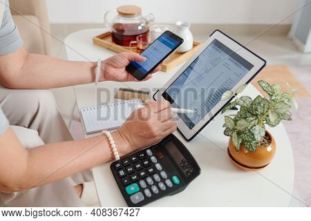 Hands Of Senior Woman Checking Investment Account Via Application On Tablet Computer And Buying New