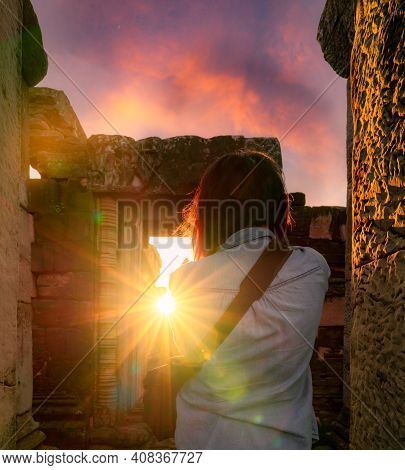 Rearview Of Woman Photographer Travel In Phimai Historical Park With Sunset Sky. Landmark Of Nakhon