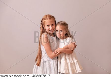 Two Sisters. Red And Blonde Girls. Sisters Embrace Each Other