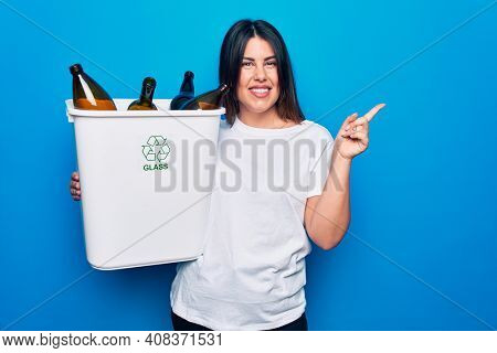 Young beautiful woman recycling glass bottles on wastebasket to care environment smiling happy pointing with hand and finger to the side