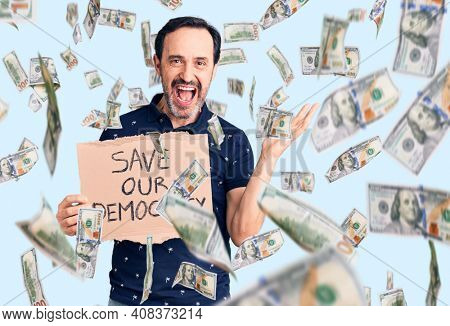 Middle age handsome man holding save our democracy cardboard banner celebrating victory with happy smile and winner expression with raised hands