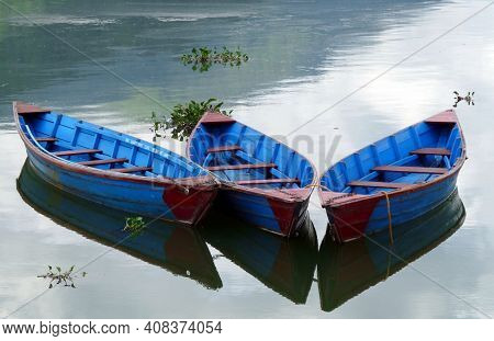 Colourful Bright Blue Rowing Boats On Tranquil Phewa Lake, Pokhara, Nepal With Clouds Reflected In W