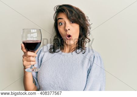 Young hispanic woman drinking a glass of red wine scared and amazed with open mouth for surprise, disbelief face