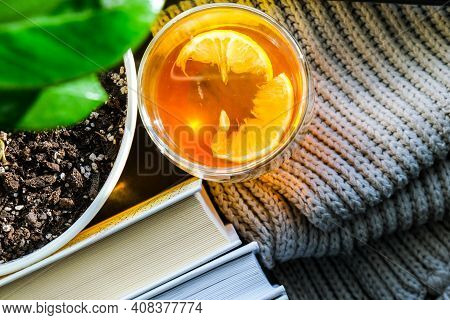 A Cup Of Hot Tea With Lemon On A Pile Of Books, Steam Comes Out Of The Cup. Yellow Flower Pot With G