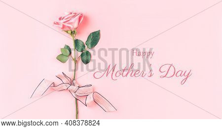 Beautiful Rose Of Pink Color Against A Pink Background. Photo Caption Happy Mothers Day. Greeting Ca
