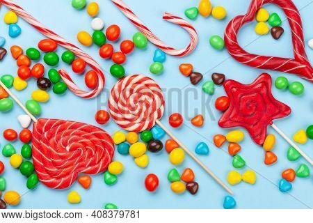 Various sweets assortment. Candy, bonbon and lollipops on blue background. Top view flat lay
