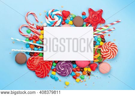 Various sweets assortment. Candy, bonbon, chocolate and macaroons over blue background. Top view flat lay with greeting card for copy space
