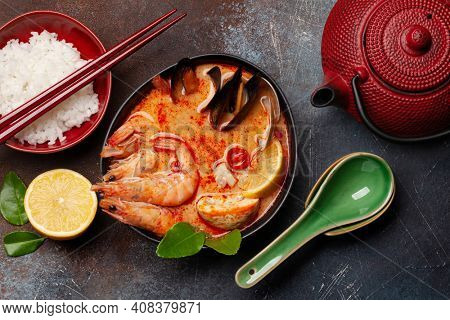 Traditional Thai soup Tom Yum kung with seafood, coconut milk and chili pepper and rice bowl. Top view flat lay