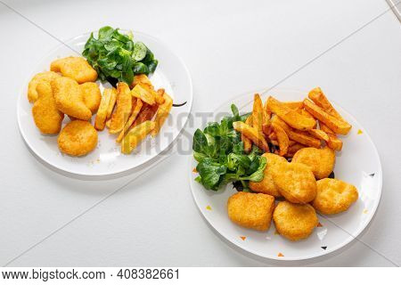 Chicken nuggets with french fries and salad for kids menu.