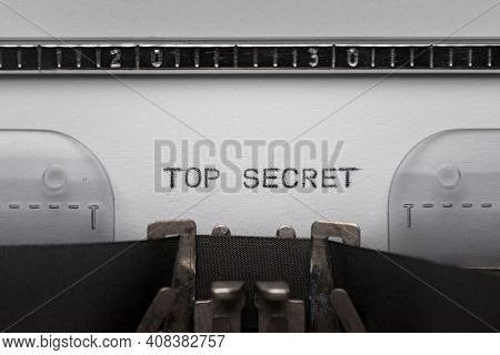 Typing text TOP SECRET on vintage manual typewriter. Close up of writes word on white paper. Shot in macro.