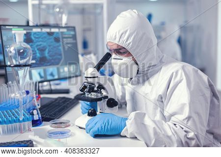 Medic Working With Microscope Analyzing Sample Using Microscope In Time Of Pandemic. Virolog In Cove