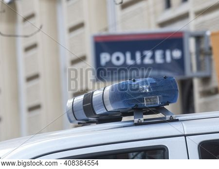 Blue Light On The Roof Of A Police Car, Police Station (polizei) Sign Blurred In The Background