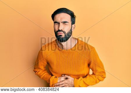 Young hispanic man wearing casual clothes with hand on stomach because nausea, painful disease feeling unwell. ache concept.