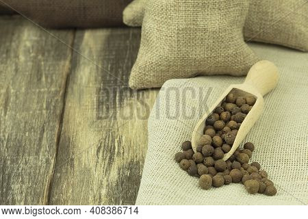 Allspice Peppers In A Wooden Spoon On A Wooden Background. Dry Allspice Grains In A Spoon And Copy S