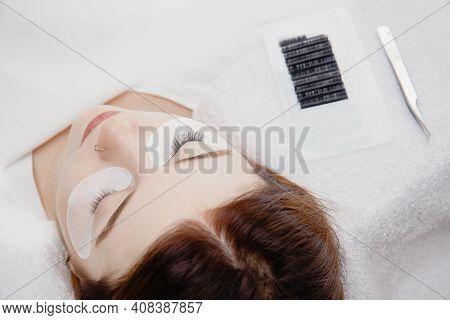 Eyelash Extension Procedure. Master Tweezers Fake Long Lashes Beautiful Woman Eyes
