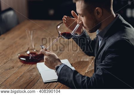 Sommelier Compiles Tasting Card Of Alcohol For Restaurant, Evaluates Red Wine In Glass