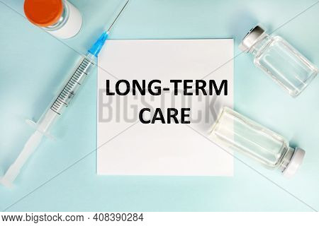 On A White Sheet The Inscription Long-term Care. Near The Sheet Is A Medical Syringe And Ampoules. T