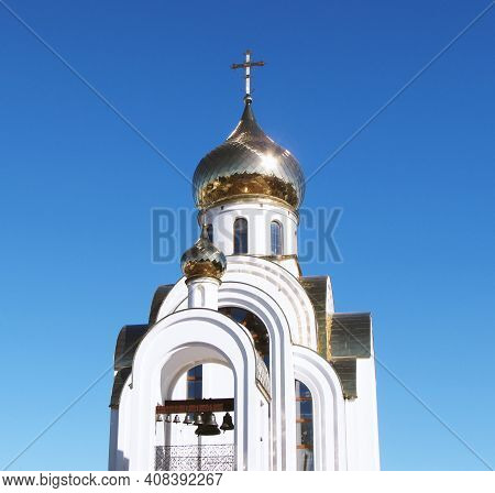 Orthodox Church With Gilded Domes. Blue Sky.