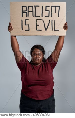 Fierce Plus Size Young African American Woman In Casual Clothes Looking At Camera, Holding Racism Is