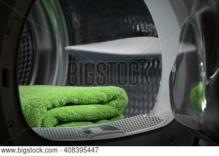 Folded Clean Green Towels In The Tumble Dryer. Clean Concept. Laundry. A Closeup Of An Open Washing