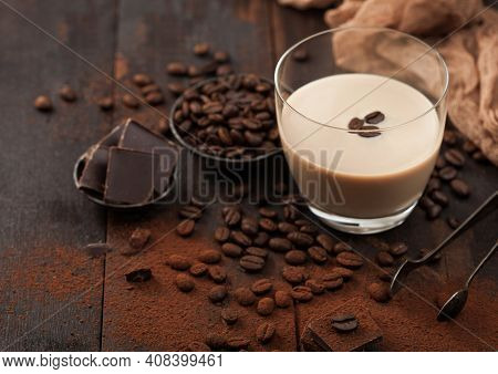 Glass Of Irish Cream Baileys Liqueur With Coffee Beans And Powder With Dark Chocolate And Brown Clot
