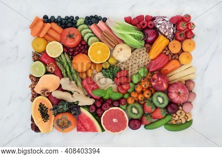 Vegan plant based fruit and vegetables for a healthy lifestyle high in antioxidants, dietary fibre, anthocyanins, vitamins, omega 3, lycopene, protein, carotenoids and protein. Top view on marble.