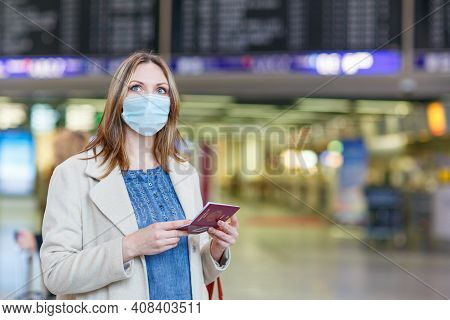 Woman With Medical Mask At International Airport, Checking Electronic Board And Waiting For Flight.