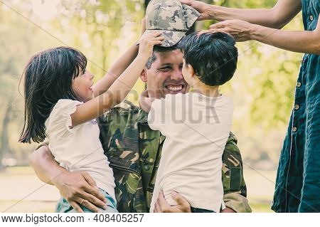 Two Happy Kids And Their Mom Meeting And Hugging Military Dad In Camouflage Uniform Outdoors. Family