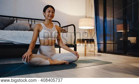 Young Asia Lady In Sportswear Doing Yoga Exercise Working Out In Living Room At Home At Night. Sport
