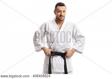 Karate man holding his black belt and smiling at the camera isolated on white background