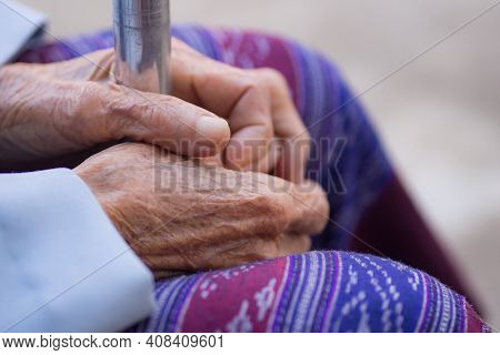 Close-up Of Hands Elderly Woman Holding Walking Stick. Focus On Hands Wrinkled Skin. Space For Text.