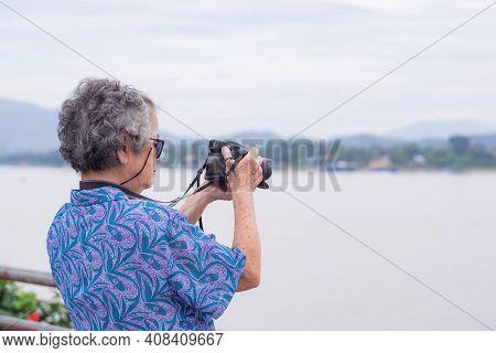Senior Woman With Short Gray Hair Wearing Glasses, Taking A Photo By A Digital Camera At The Riversi