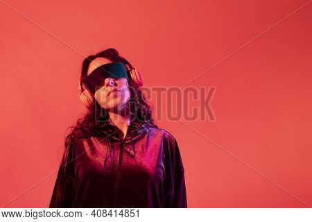 Young Girl Wearing Galactic Glasses And Headphones With Her Neck Tilted To The Side, Against Red Bac