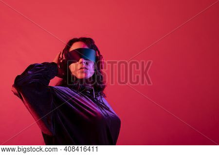 Young Girl Wearing Galactic Glasses And Headphones With Her Arm Behind Her Head, Against Red Backgro