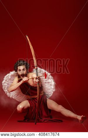 Valentine's Day concept. Full length portrait of the God of love - Cupid aiming with bow and arrow on a red background. Copy space.