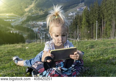 Cute Little Caucasian Kid Laying At Green Grass And Looking At Mobile Phone With Interested Face, Su