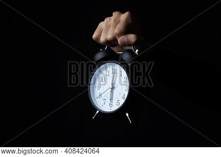 Human Hand Holding Alarm Clock In The Dark, Copy Space.