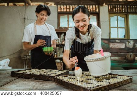 Asian Woman Smiles Wearing An Apron While Pouring The Cake Batter On The Cake Tin On The Table