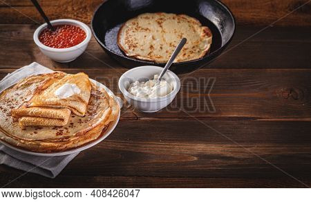Traditional Russian Crepes Blini Stacked In Plate And Cast-iron Frying Pan With Red Caviar, Fresh So