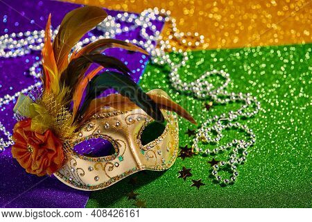 Festive, Colorful Mardi Gras Or Carnivale Mask And Beads On Golden, Green And Purple Background. Ven