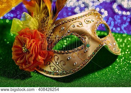Festive, Colorful Mardi Gras Or Carnivale Mask And Beads On Golden, Green And Purple Background, Clo