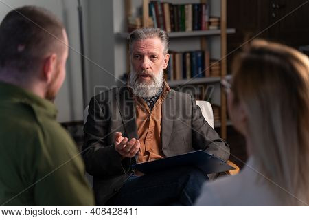 Young Married Couple For A Consultation With A Psychotherapist. An Adult Gray-haired Therapist Sits