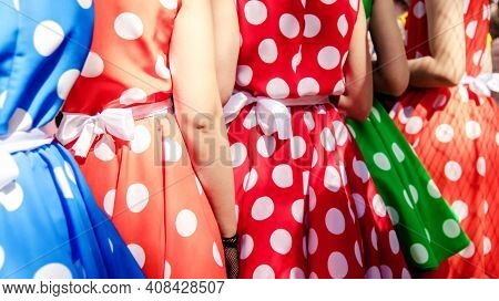 A Group Of Young Girls In Multi-colored Dresses With Polka Dots. Retro Fashion Of Red And Blue Dress