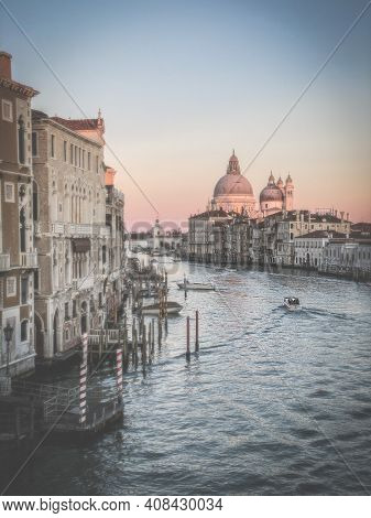 View of a boat sailing on the Grand Canal and Basilica Santa Maria della Salute from the Ponte dell'Accademia in Venice, Italy